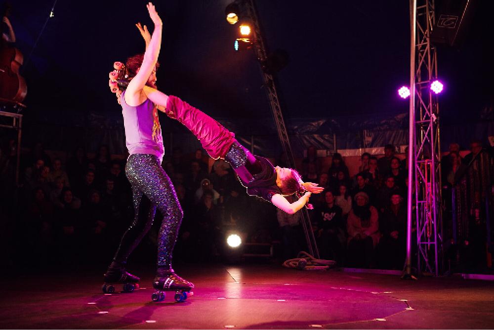 Två personer som gör cirkuskonster framför publik och i rosa strålkastarljus